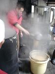 大釜で炊いた大豆をひしゃくでざるにあげます。熱っ!